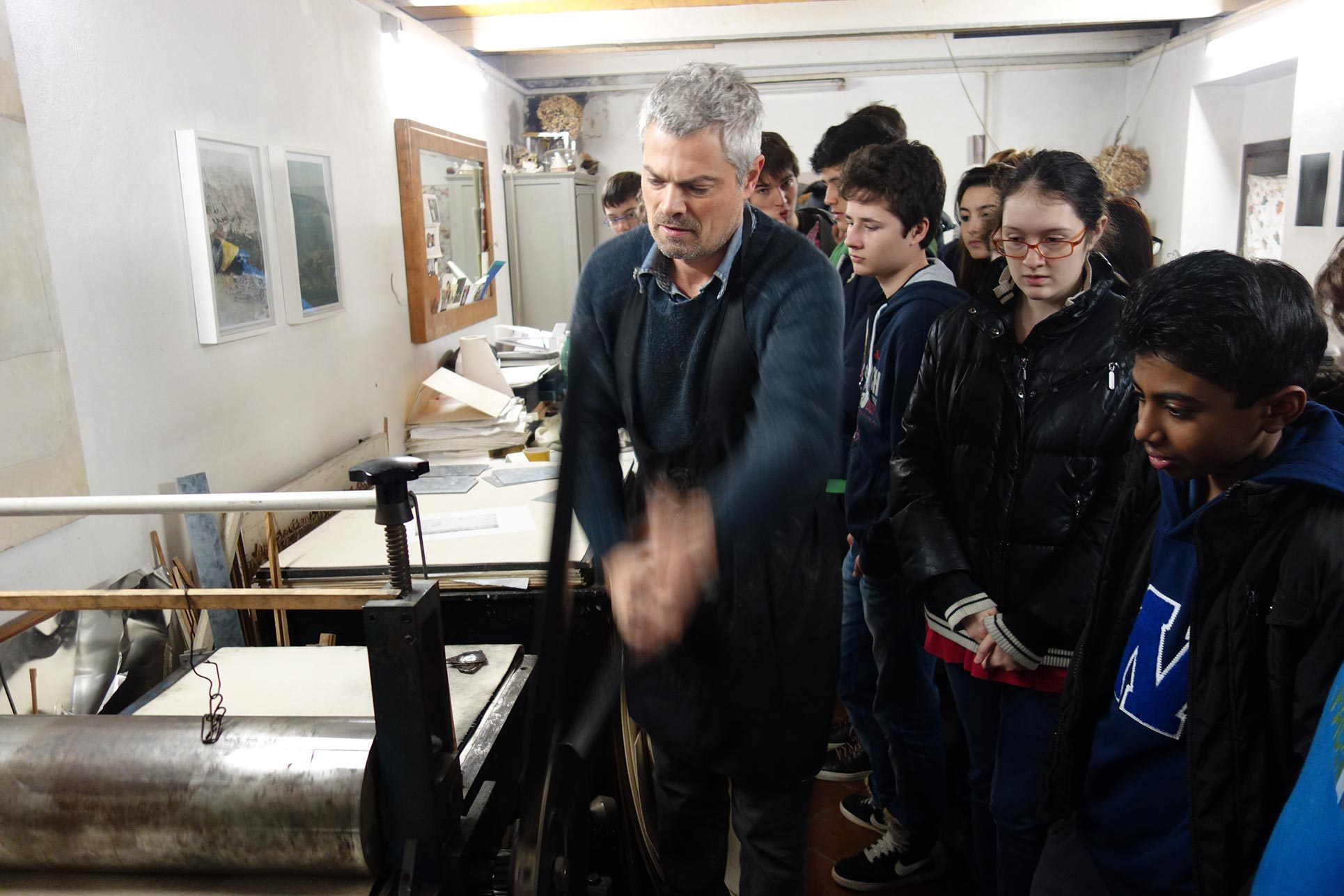 Tancredi Mangano demonstrates how his etching press functions, to the pupils. (Photo: Barbara Fässler)